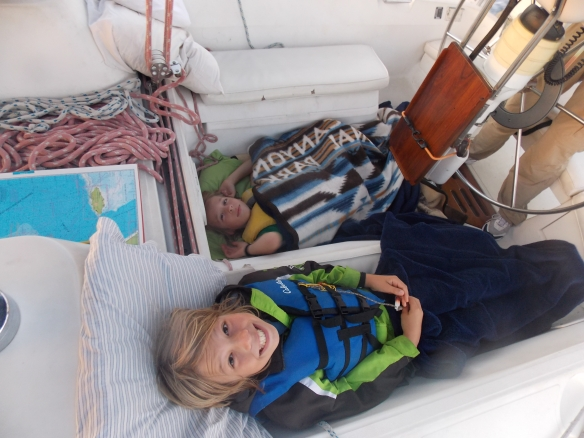 Crew waking up in the morning.  They opt to sleep in the cockpit where seasickness is not so apt to get you.  Logan woke up several times throughout the night to help out with the passage.  Cole has liked sleeping on the floor of the salon or the cockpit since he was a baby.  We are just careful not to step on him!