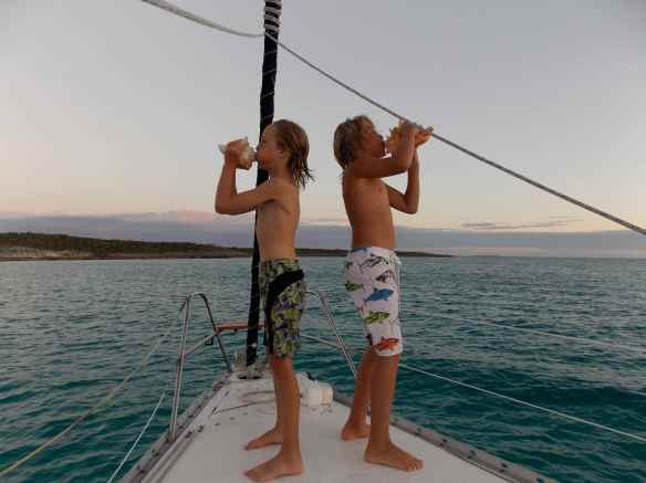 Cole & Logan blowing conch shells.