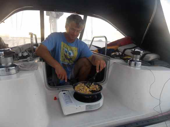 Mark cooking on our camp stove in the companionway.