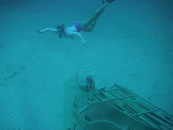 Christine diving with the mermaid at grand piano sculpture off west side Musha Cay.