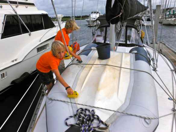 Cole and Logan cleaning the algae and barnacles off the dinghy.