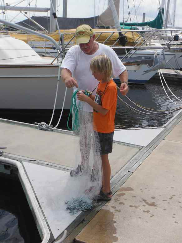 Jesse teaching Cole how to throw a cast net to catch bait.