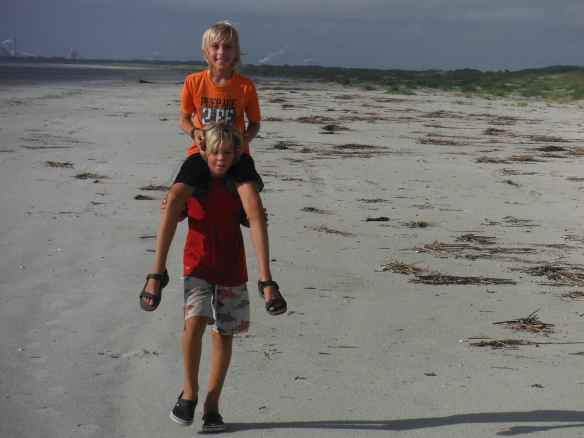Just plain having fun. Logan carrying Cole on the beach.