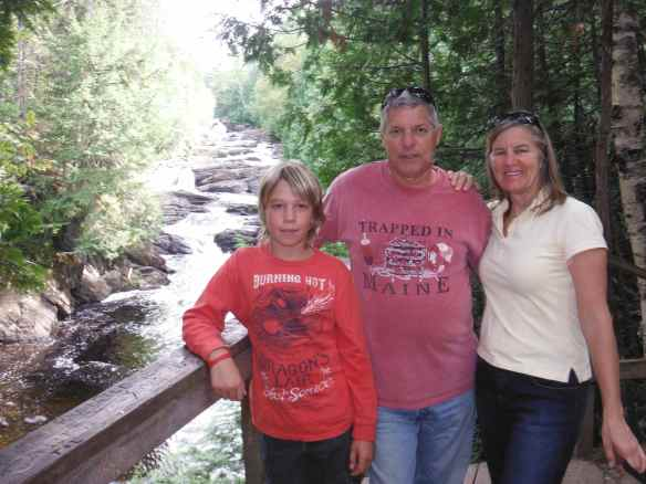 Logan with Don and Debbie at a falls on a hike.